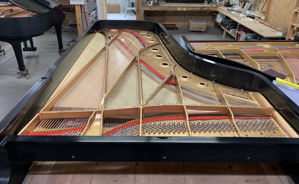 Steinway Concert Grand with new soundboard, strings, pins and pin block.